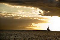 A lone sailboat silhouetted against the sunset at Ke'e Beach on the North Shore of Kaua'i.