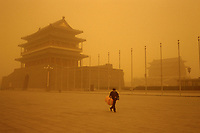 A lone man walks past Qianmen Gate near Tiananmen square in Beijing. When dust storms strike the capital, they turn the sky an amber color and reduce visibility to about 1/3 mile. Extensive deforestation and desertification in northern China have fueled the dust storms. Nearly one million tons of Gobi Desert sand blows into Beijing each year.