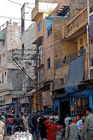 Typical street scene in New Delhi, India.  Notice the maze of wires strung from building to building