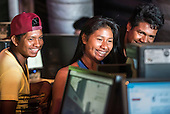 Three young indigenous people share a funny Facebook post in the Digital House at the International Indigenous Games, in the city of Palmas, Tocantins State, Brazil. Photo © Sue Cunningham, pictures@scphotographic.com 28th October 2015
