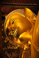 The gilded FACE of the largest RECLINING BUDDHA in THAILAND (46 meters long) which is found at the THERAVADA BUDDHIST TEMPLE of WAT PO - BANGKOK, THAILAND