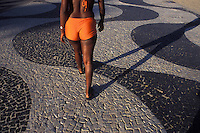 View from behind of sensual young black woman walking at Copacabana pedestrian walkway ( calçadão de Copacabana ) wearing short  - Rio de Janeiro - Brazil.