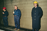 Switzerland. Canton Lucerne. Three bored men in the Sonnenberg tunnel in Lucerne during the largest civil defense exercise ever held in the country. From 16 to 21 November 1987, almost 1200 men and women converted a motorway tunnel into perhaps the world's largest bunker structure. The civil protectors had to prove during the exercise «Ameise » ( Ants in english) that in an emergency more than 20,000 inhabitants of the city of Lucerne could survive here in the mountain for two weeks. The Sonnenberg Tunnel is a 1,550 m  long motorway tunnel, constructed between 1971 and 1976. At its completion it was also the world's largest civilian nuclear fallout shelter, designed to protect 20,000 civilians in the eventuality of war or disaster. Based on a federal law from 1963, Switzerland aims to provide nuclear fallout shelters for the entire population of the country. The construction of a new tunnel near an urban centre was seen as an opportunity to provide shelter space for a large number of people at the same time. The giant bunker was built between 1970 and 1976 at a cost of 40 million Swiss francs. The shelter consisted of the two motorway tunnels (one per direction of travel), each capable of holding 10,000 people in 64 person subdivisions. A seven story cavern between the tunnels contained shelter infrastructure including a command post, an emergency hospital, a radio studio, a telephone centre, prison cells and ventilation machines. The shelter was designed to withstand the blast from a 1 megaton nuclear explosion 1 kilometer away. The blast doors at the tunnel portals are 1.5 meters thick and weigh 350 tons. The logistical problems of maintaining a population of 20,000 in close confines were not thoroughly explored, and testing the installation was difficult because it required closing the motorway and rerouting the usual traffic. The only large-scale test, a five-day exercise in 1987 to practice converting the road tunnels into usable shelters, revealed many pro