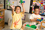 Preschool ages 3-5 pretend play boy flying his creation made from colored connecting plastic cubs as friend plays nearby horizontal