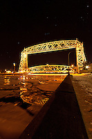 Large plates of ice slowly float under Duluth's Aerial Lift Bridge on a late winter evening.