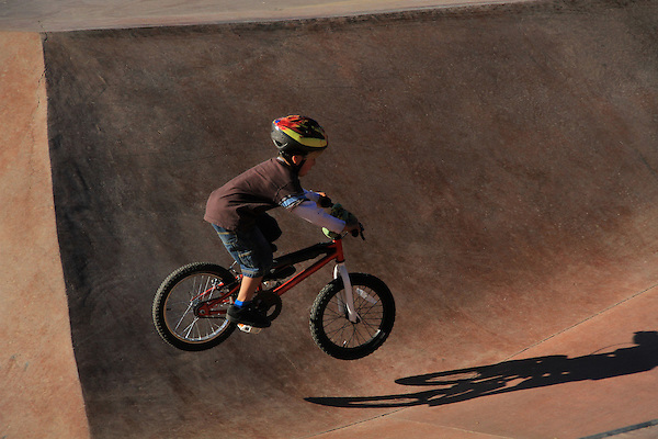 Boy jumping his bike in a skateboard park in Denver, Colorado. .  John offers private photo tours in Denver, Boulder and throughout Colorado. Year-round.