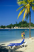 Negril, Jamaica. Tourist couple on the beach at Sandals resort with palm tree and colourful sails.