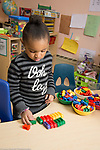Education Preschool 3-4 year olds girl at table sorting and lining up colored plastic trucks by color