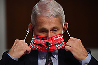 Dr. Anthony Fauci, director of the National Institute for Allergy and Infectious Diseases, lowers his face mask as he prepares to testify before the Senate Health, Education, Labor and Pensions (HELP) Committee on Capitol Hill in Washington DC on Tuesday, June 30, 2020.  Fauci and other government health officials updated the Senate on how to safely get back to school and the workplace during the COVID-19 pandemic. Credit: Kevin Dietsch/CNP/AdMedia