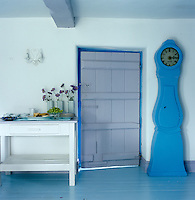 A blue-painted Swedish Mora clock stands on a blue-painted wooden floor beside a blue-framed door