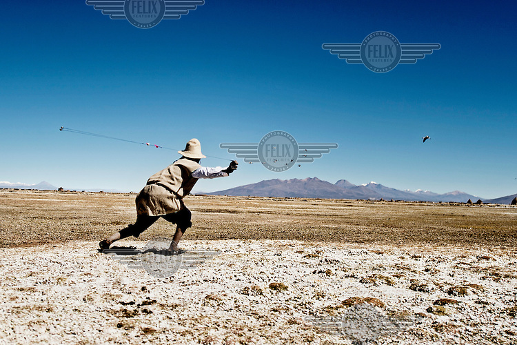 As a low flying flock of flamingos approaches, Jose Luis Mamani Chino leaps to his feet and swings his sconi throwing weapon, versions of which are used throughout the Andes. The brightly coloured bits of thread make it easier to find after it has been flung.