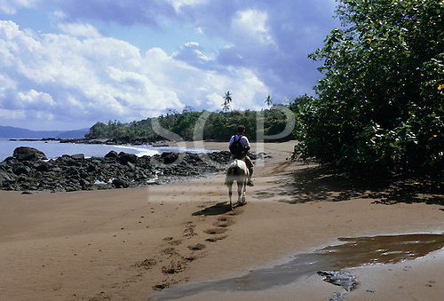 Osa Peninsula, Costa Rica. Single tourist riding a horse on the beach at Drake Bay with rocks to seaward and rainforest inland.