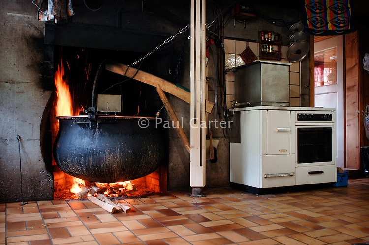 Copper cauldron full of 400 litres of curdling milk, heating on the fire in the kitchen of the mountain chalet.?   Cowherd and cheesemaker spends 100 days in the summer, high up in the mountains, tending cows and pigs and making cheese at Balisalp and Käserstatt near Meiringen, Switzerland.