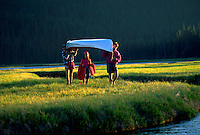 A family carries a canoe on the lush, green embankments of a river.
