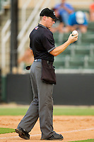 Home plate umpire Junior Valentine checks a baseball to see if it is still playable during the South Atlantic League game between the Rome Braves and the Kannapolis Intimidators at CMC-Northeast Stadium on August 5, 2012 in Kannapolis, North Carolina.  The Intimidators defeated the Braves 9-1.  (Brian Westerholt/Four Seam Images)