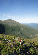 Hiker ascending the Six Husbands Trail in Thompson and Meserve's Purchase, New Hampshire during the summer months; part of the Presidential Range in the White Mountains. Named after John Adams, 2nd President of the United States, Mount Adams is in the background.