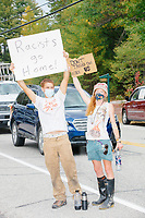 """People hold signs reading """"Racists go home!"""" and """"Don't Tread on Us / Biden"""" as Donald Trump, Jr., son of president Donald Trump and a rising Republican political star, leaves after speaking at an outdoor campaign rally at The Lobster Trap in North Conway, New Hampshire, on Thu., Sept. 24, 2020."""