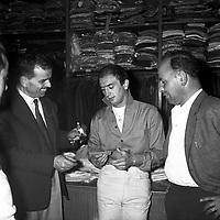 """1er juillet 1959. Pierre Lacaze, surnommé """"Papillon"""" vient de signer avec le club Toulouse Olympique XIII (rugby à XIII).<br /> <br /> Plan taille sur le joueur qui tient sa licence dans la main (vue de face) ; il est entouré de deux hommes (président du club?)."""