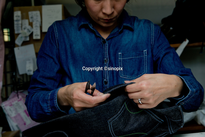 MAY 16, 2014 - KOJIMA, KURASHIKI, JAPAN: A worker inspects hand made ordered jeans at the Betty Smith's factory. (Photograph / Ko Sasaki)