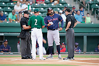 Manager Iggy Suarez (2) of the Greenville Drive meets with manager Kaneoka Texeira (50) of the Rome Braves, home plate umpire Joe Belangia and field umpire Dylan Bradley  before a game on Wednesday, August 4, 2021, at Fluor Field at the West End in Greenville, South Carolina. (Tom Priddy/Four Seam Images)