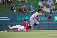 Third baseman Dustin Harris (9) of the Hickory Crawdads reaches for the throw from the outfield as Don D'Alessandro (17) of the Greenville Drive reached third safely in a game on Friday, August 27, 2021, at Fluor Field at the West End in Greenville, South Carolina. (Tom Priddy/Four Seam Images)