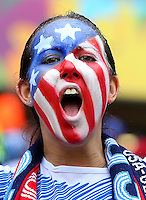 A USA fan with painted face cheers her side on
