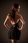 Young woman wearing black dress with hands on hips