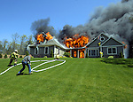 (Winner National Press Photographers Ascc Spot News) Video at You Tube of these photos http://www.youtube.com/watch?v=QRtfDhBJuuk&feature=youtube_gdata<br /> <br /> <br /> Fire engulfs this large contemporary style home at 27 Abbott Rd in Ellington, CT., Sunday, April 29, 2012. The fire was blowing out of the rear enclosed porch (on my arrival) before a large flash over consumed the house. The house is new construction but the fire had already consumed much of the house before Ellington Fire Department. was on scene. Two occupants and the family dog escaped the house prior to the fire Department arrival, so this was an exterior operation all the way, Strong winds caused a fairly large brush fire behind house into the wood line. Vernon, Crystal Lake, Tolland and South Windsor fire departments were on scene assisting the Ellington Fir Department..Check out pictures of the EFD trying to save the house. (Jim Michaud/@CTNewsAlert)