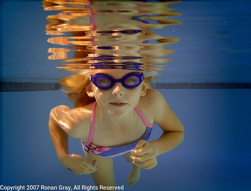 Young girl wearing googles swimming just below the surface of a pool with reflection on the underside of the water