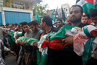 """Mourners carry the bodies of four Palestinian children from the Abu Maateq family during their funeral in Beit Lahia in the northern Gaza Strip on April 28, 2008. Four children, aged one to five, their mother and a militant were killed in Israeli operations in Gaza today as Palestinian factions headed to Egypt for talks on a possible truce. The four siblings -- aged one, three, four and five -- were killed when a tank shell hit their home in the town of Beit Hanun, and their mother died later of her wounds, doctors at the Kamal Radwan hospital said.""""photo by Fady Adwan"""""""