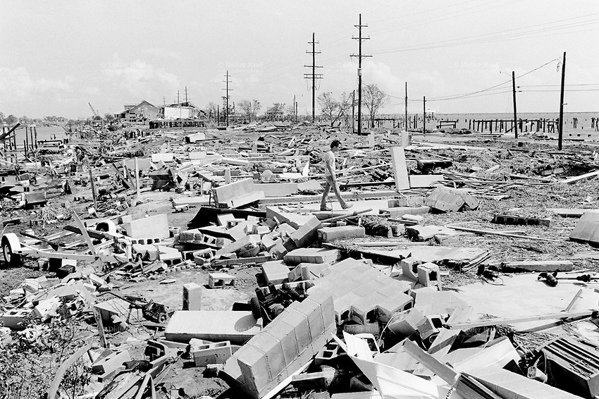 USA. Louisiana. Slidell. Aftermath of hurricane Katrina. Marina area near the lake Pontchartrain is virtually destroyed . Most houses were  destroyed by the storm, the tidal surge (water wave) and the floods. A man walks among the houses' ruins. The area is now empty and all its inhabitants have left away. The people could no longer and ever live again in the houses. The entire area needs to be bulldozed before any new construction can be built. Household waste. Destruction of the urban american way of life. © 2005 Didier Ruef