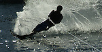Beautiful silohuette of a water skier slicing through the water.