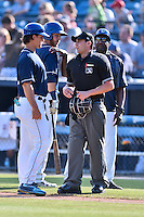 Asheville Tourists manager Warren Schaeffer (13) discusses a controversial call with home plate umpire Anthony Perez while Mike Devereaux calms Brian Mundell (15) during a game against the West Virginia Power at McCormick Field on June 25, 2016 in Asheville, North Carolina. The Tourists defeated the Power 8-4. (Tony Farlow/Four Seam Images)
