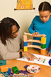 7 year old girl with mother activity building colorful wooden marble run using visual directions vertical
