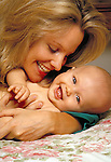 young mother playing with laughing, happy newborn infant