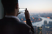 A man uses a smartphone to photograph an aerial view of London from Level39, which occupies the entire 39th floor of the iconic tower at One Canada Square, and describes itself as Europe's largest accelerator space for finance, retail and future cities technology companies.  It is part of the London Tech City initiative, and was set up by the Canary Wharf Group in March 2013 to put high potential tech developers in the same space as influential technology buyers and investors.