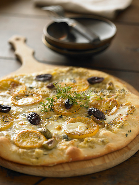 Gourmet pizza with artichoke pesto, olives, and lemon.