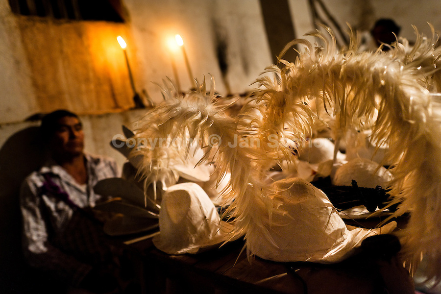 """A Cora Indian man guards feather hats during the religious ritual celebration of Semana Santa (Holy Week) in Jesús María, Nayarit, Mexico, 21 April 2011. The annual week-long Easter festivity (called """"La Judea""""), performed in the rugged mountain country of Sierra del Nayar, merges indigenous tradition (agricultural cycle and the regeneration of life worshipping) and animistic beliefs with the Christian dogma. Each year in the spring, the Cora villages are taken over by hundreds of wildly running men. Painted all over their semi-naked bodies, fighting ritual battles with wooden swords and dancing crazily, they perform demons (the evil) that metaphorically chase Jesus Christ, kill him, but finally fail due to his resurrection. La Judea, the Holy Week sacred spectacle, represents the most truthful expression of the Coras' culture, religiosity and identity."""