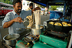 Indian street cook preparing tea and streetfood (pakora, fritters) in his small mobile cook-shop. Fort Cochin (Kochi), Kerala, India.