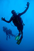 Scuba divers making faces for the camera, Ross Atoll, Maldive Islands.