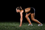 Young woman exercising, stretching and running on grass with black background.  MODEL RELEASED
