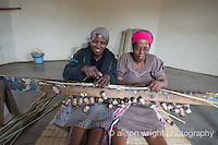 Africa, Swaziland, Malkerns.Nest organization artisan project, partnering with Gone Rural & local artisans to help market their products to global markets and better sustain their local community. Emmah Manana, works as artisan at Rosecraft, is also leaning how to use a camera to shoot her products. She's working the homemade loom (made with strings & old batteries) with her mother, Linah (pink hat), at home in their 8 corner house. Emmah learned the art of weaving from her mother who makes these grass mats used for sleeping and to wrap the dead in. Emmah with her mother pink hate) and daughter, Tegebeni Dlamini (14 yrs).The money she earns helps her family to build this house and send the children to school.