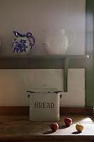 An enamel bread bin below a row of jugs in the kitchen
