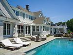Contemporary shingle-style coastal home estate. Backyard swimming pool setting.
