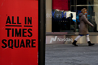 NEW YORK, NEW YORK - MARCH 10: A woman walks in front Nasdaq at Times Square on March 10, 2021, in New York. The Nasdaq Composite continued falling more than half a percent during the day also the move away from Apple Inc, Amazon.com Inc , Facebook Inc, Tesla Inc and Microsoft Corp, falling during the day, helped small-cap stocks rise more than double the gains of the S&P 500. (Photo by John Smith/VIEWpress)