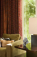Detail of a moss green club chair with animal skin cushions in front of the brown striped curtains in the living room