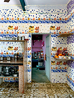 The kitchen is a riot of colour and pattern.  Marble has been used for worktops and open shelving to store pots, pans, bowls, cups and items in daily use, while the pink-painted pantry houses dry goods, such as lentils and spices