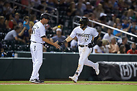 Charlotte Knights manager Mark Grudzielanek (15) slaps hands with Danny Mendick (17) as he rounds third base after hitting a home run against the Gwinnett Braves at BB&T BallPark on July 12, 2019 in Charlotte, North Carolina. The Stripers defeated the Knights 9-3. (Brian Westerholt/Four Seam Images)