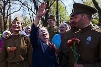 Moscow, Russia, 09/05/2013..A Russian World War Two veteran in Gorky Park waves to military planes flying overhead while singing with well-wishers wearing Soviet era army uniforms during the country's annual Victory Day celebrations.