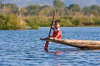 Myanmar, Burma.  Little Burmese Boy on Canoe with Paddle, Inle Lake, Shan State.